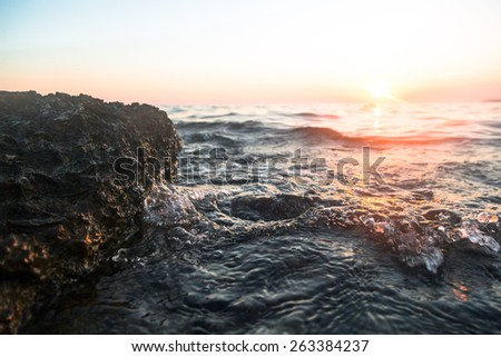 ocean wave falling down at sunset time - stock photo