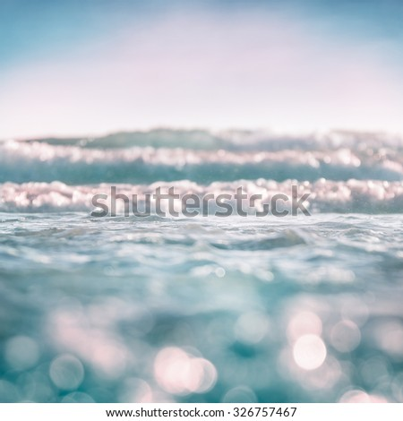 Ocean waves and surf with bokeh effects in the foreground.  Image features soft, selective focus with subtle cross-processing. - stock photo