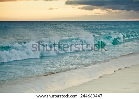 Ocean waves breaking at Cape Verde sandy beach in summer on a sunny evening - stock photo