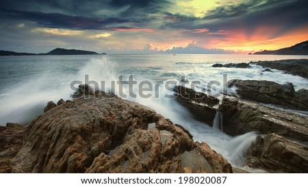 Ocean waves crashing onto the rocks in the sunset - stock photo
