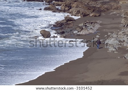 Ocean waves nearly reach a lone man walking on sand along rocky shore - stock photo