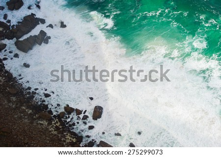 Ocean waves shot from above. The water is turquoise color and foamy. You can also see the rocky shore.  - stock photo