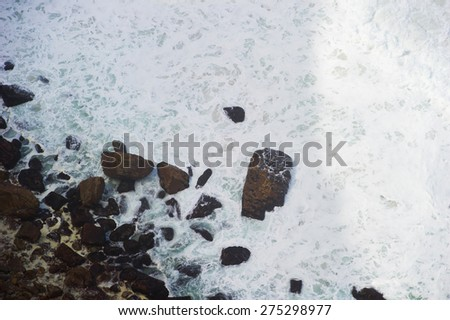 Ocean waves shot from above. The water is white and foamy. You can also see the rocky shore.  - stock photo