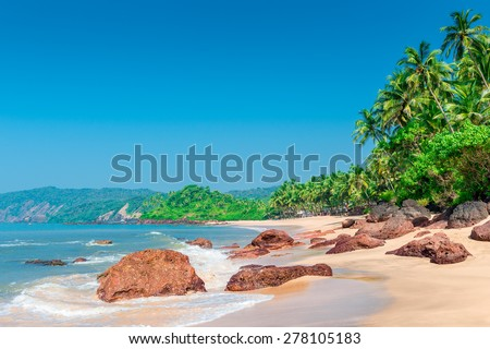 ocean waves wash shore a tropical beach - stock photo