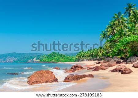 ocean waves wash shore a tropical beach - stock photo