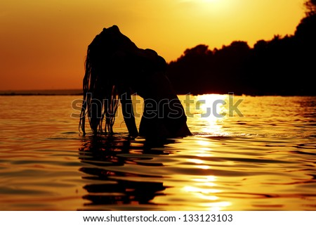 ocean woman in sunrise light - stock photo