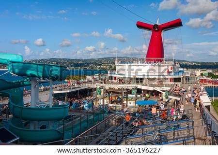 OCHO RIOS, JAMAICA - 09 APRIL 2008: Carnival Conquest large cruise ship was docked at the coast of Jamaica. Panoramic view from the upper pool deck. - stock photo
