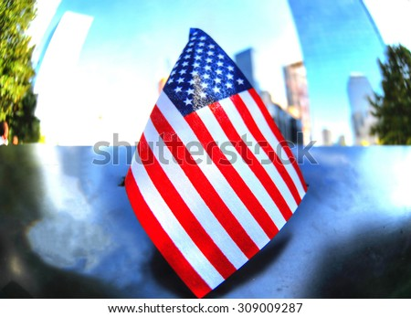 Oct 14, NYC, USA: Fisheye image (selective focus) - focusing a small USA flag over the memorial site of the 9/11 terror attack. It was taken in the 911 memorial site on Oct 14, 2014, NYC, USA - stock photo