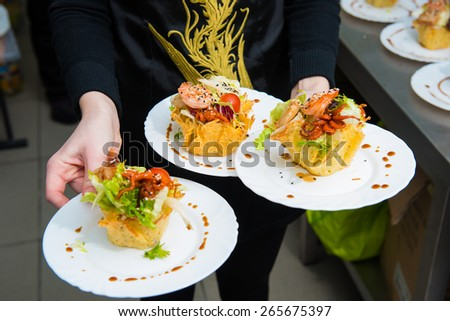 Octopus appetizer with small potatoes. three plates with a snack in the hands of the cook - stock photo