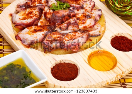 Octopus with paprika, potatoes and olive oil typical of Galicia, Spain ...
