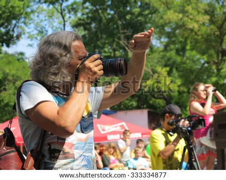ODESSA - MAY 30, 2015: The gray-haired tanned male photographer at work in the park, sunny day May 30, 2015 in Odessa, Ukraine - stock photo