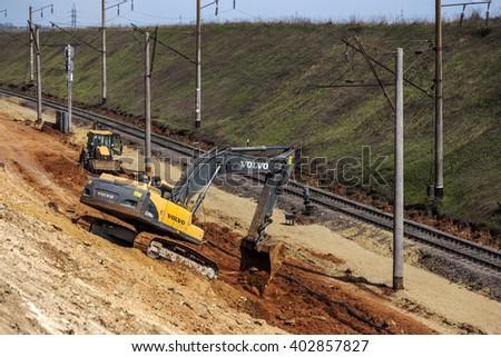 ODESSA, UKRAINE - April 7, 2016: Workers using heavy machinery repairing the railway line. Excavators, special technique on reconstruction of the railway rails - stock photo