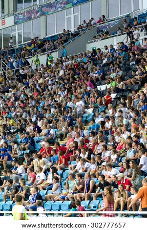 ODESSA, UKRAINE - August 2, 2015: Football fans and spectators in the stands of the stadium emotionally support their team during the game FC Dynamo Kyiv - Chernomorets Odessa. Major League. - stock photo