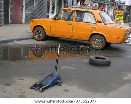 Odessa, Ukraine, February 10, 2016 -: Replacing wheels on a car, jack holds the body in raised position, on a road in the city centre - stock photo