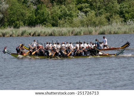 Odessa, Ukraine - May 16, 2010: Championship of Ukraine rowing among veterans. Dragon boat on the river. People rowing boat in the race in the summer - stock photo