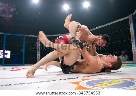 Odessa, Ukraine - November 24: Athletes compete in the MMA cage, resulting in punching, kicking and wrestling. The dramatic moment of battle November 24, 2015 in Odessa, Ukraine - stock photo