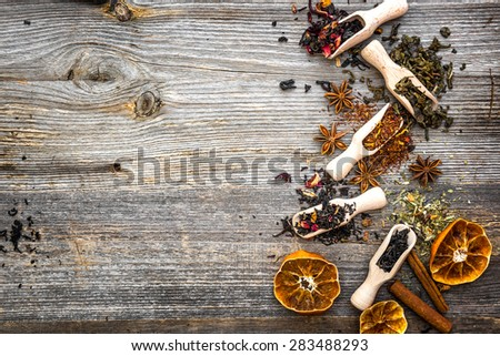 odorous dry teas in scoops on wooden background - stock photo