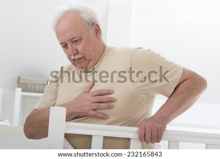 oerweight senior man' hand grabbing his  chest - stock photo