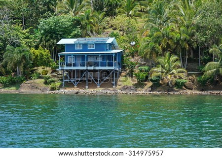 Off grid coastal home with lush tropical vegetation, Caribbean shore of Panama, Bocas del Toro, Central America - stock photo