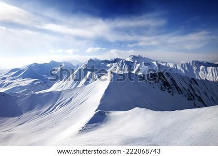 Off-piste slope and sunlight sky. Caucasus Mountains, Georgia, ski resort Gudauri. Wide angle view. - stock photo