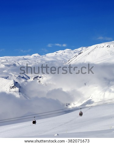 Off-piste snowy slope and cable car at sun day. Caucasus Mountains, Georgia, region Gudauri. - stock photo