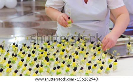off-premise catering - waitresses put fruit canapes on buffet table - stock photo