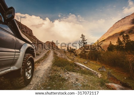 Off-road car on mountain road - stock photo