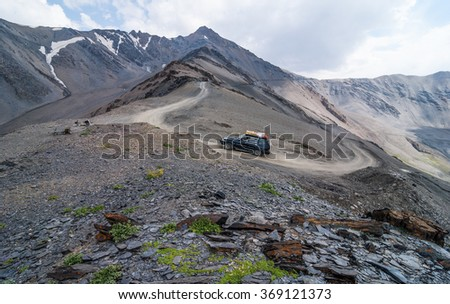 Off-road vehicle on the road to mountain pass - stock photo