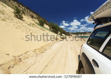 Off road vehicle with surfboard on roof driving on tropical beach - stock photo