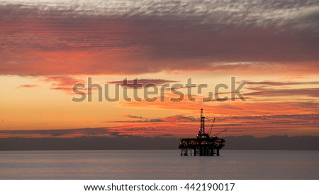 Off-shore oil platform at sunset. - stock photo