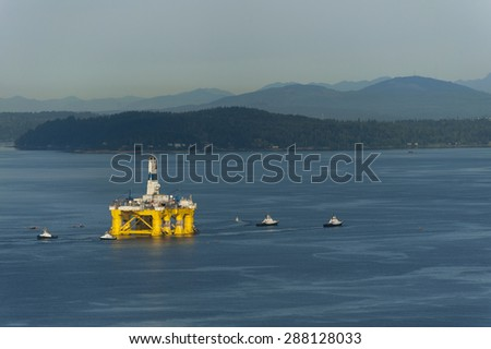 Off Shore Oil Rig. Tug boats escort an off shore oil drilling rigs as it leaves Seattle, Washington to return to Alaska. - stock photo