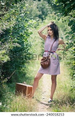 Off to elsewhere: beautiful young woman thinking about her next destination - stock photo