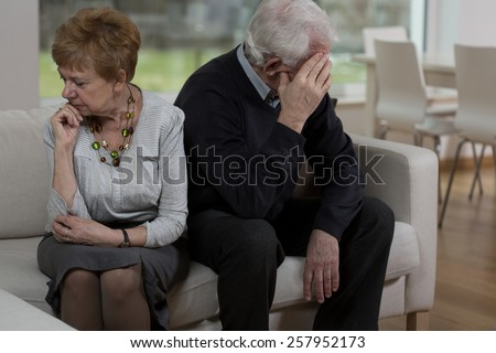 Offended elder couple sitting on the sofa - stock photo