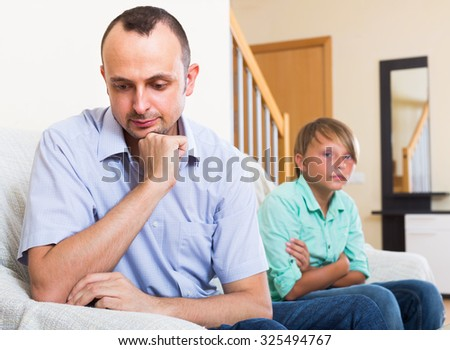 Offended man having domestic problems with son - stock photo