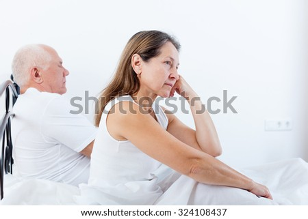 offended woman sitting on   bed next to   frustrated man. - stock photo