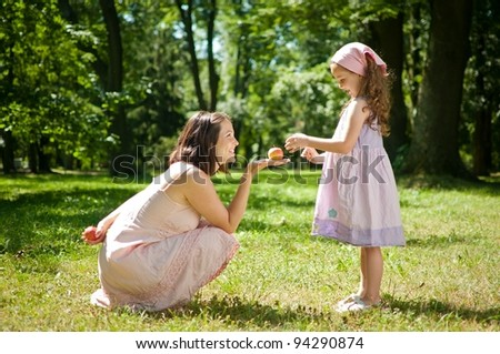 Offering apple - mother with child - stock photo