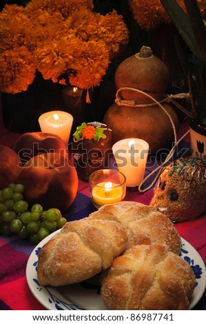 "Offering as part of the celebration of the day of the dead in Mexico ""Dia de muertos"" with bread ""Pan de Muerto"" chocolate and amaranth skulls and flowery in background. - stock photo"