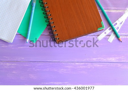 Office and school supplies on a table. Open notebook, folder for papers, brown notepad, pencil, two files, pen on wooden background with blank place for text. Top view  - stock photo