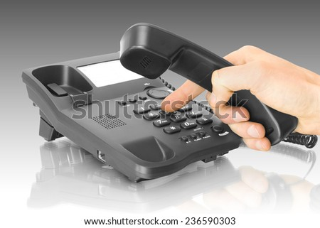 office black telephone with hand and dialing finger - stock photo