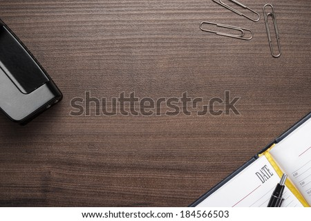 office brown wooden table with pen and notebook background - stock photo