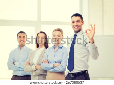office, business, and teamwork concept - friendly young smiling businessman with team on back showing ok-sign - stock photo