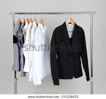 Office clothes on hangers, on gray background - stock photo
