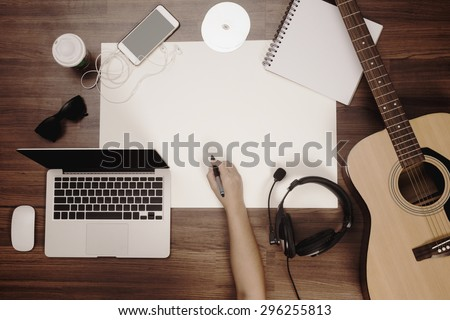 Office desk background, Hand drawing on blank poster with acoustic guitar and headphones recording scene project ideas concept, With laptop computer, cup of coffee. View from above with copy space - stock photo