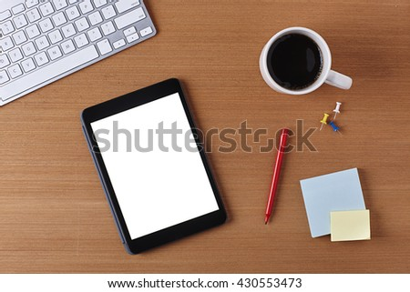 Office Desk Table with a Blank Tablet, keyboard, cup of coffee, red pen, blank piece of paper and supplies. Workplace Top View on a Wooden Background with Copy space for text or Image - stock photo
