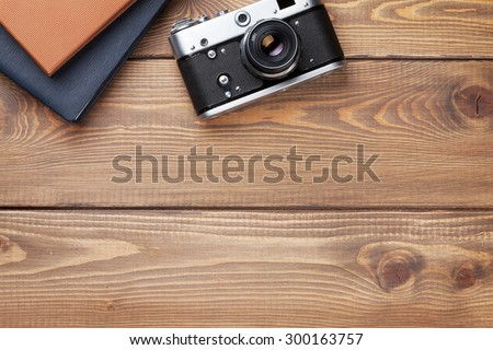 Office desk table with camera and notepad. Top view with copy space - stock photo