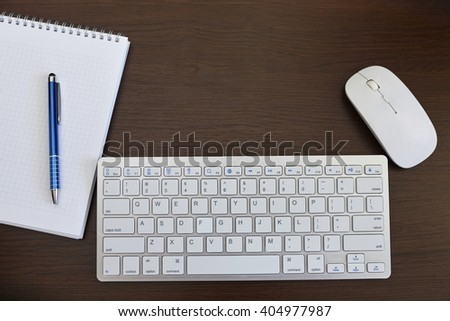 Office desk table with computer, mouse and supplies - stock photo
