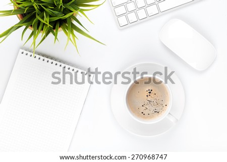 Office desk table with computer, supplies, coffee cup and flower. Top view with copy space - stock photo