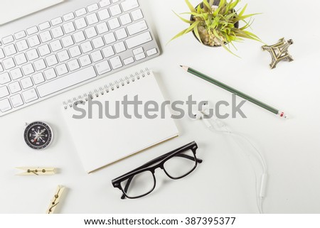Office desk table with computer, supplies, flower,glasses,pencil,compass,blank note book. Top view with copy space,White office desk table with a lot of things on it. Top view with copy space. - stock photo
