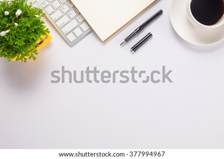 Office desk table with computer, supplies, paper, pen, cup of coffee and flower. Top view with copy space (selective focus) - stock photo