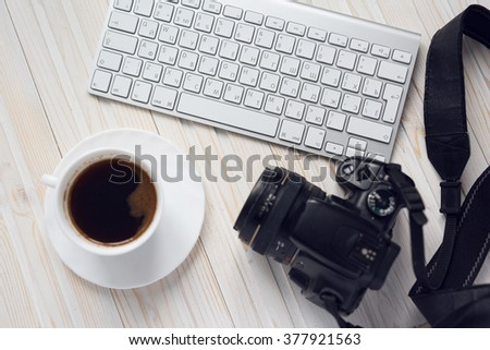 Office desk table with keyboard, cup of coffee and camera  - stock photo